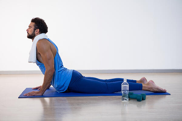 Man doing cobra pose on exercise mat in fitness studio Put this time to good use by taking a virtual exercise, yoga or meditation class to get your endorphins pumping and the correct mindset