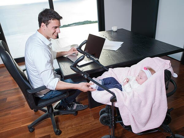 effective remote working a young man parent working on laptop computer at home office and take care of baby