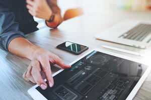 Website designer working digital tablet and computer laptop with smart phone and graphics design diagram to optimise on all devices
